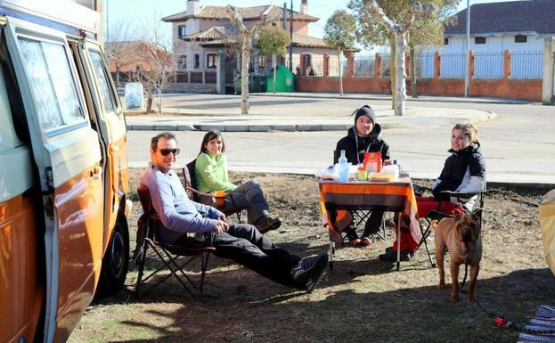 Cuatro participantes disfrutan de un avituallamiento en Torquemada en el 'jardín de su casa rodante'. /Luis A. Curiel