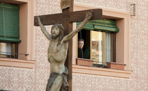 Unos vecinos observan el paso del Santísimo Cristo por su calle. /Óscar Costa