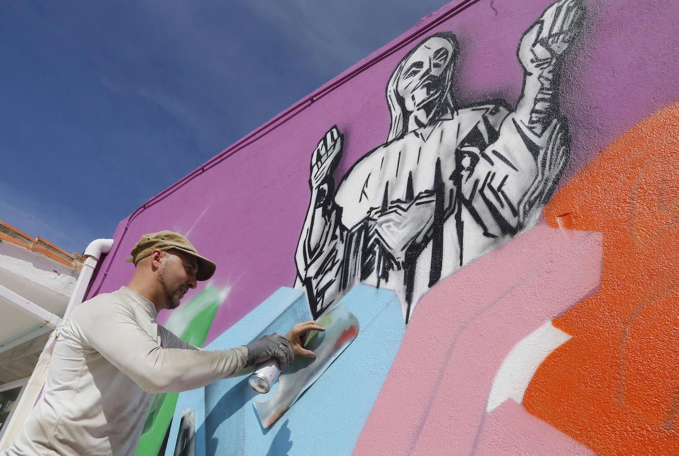 Chisco trabaja ayer en su mural en el área de caravanas de la carretera de León. /Marta Moras
